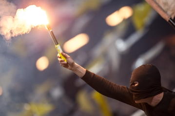 Passionate AIK supporter burning pyrotechnics.